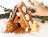Hand decorating gingerbread house — Stock Photo