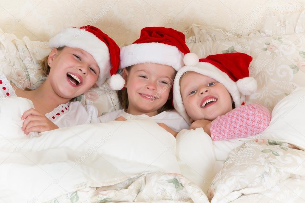 Laughing little girls in bed with santa hats on  Stock Photo #13603500