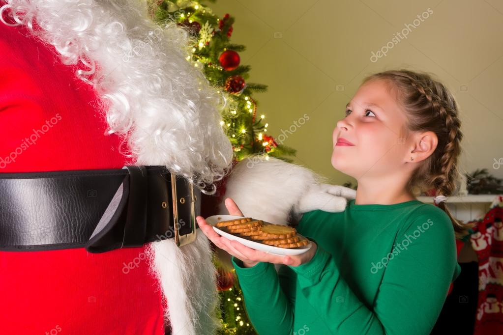 Adorable girl presenting cookies to santa claus — Stock Photo #13603527