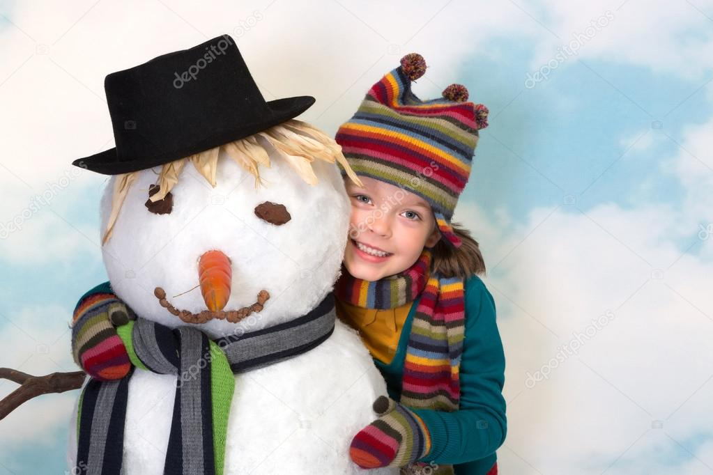 Happy little girl hugging her lifesize snowman — Stock Photo #13603530