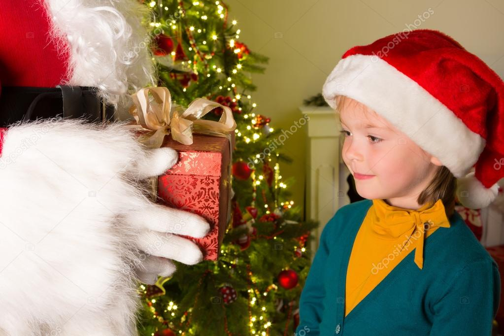 Little 5 year old girl getting a red gift from santa claus  Foto de Stock   #13900080