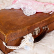 Grungy suitcase and lace lingerie — Stock Photo