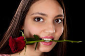 Woman with red rose in her mouth — Stok fotoğraf