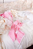 Pink baby-doll on bed — Stock Photo