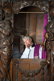 Priest in confession booth — Stock Photo