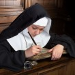 Ancient book and young nun — Stock Photo
