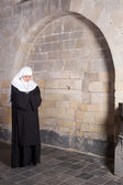 Young nun in old church — Stock Photo