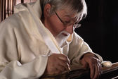 Ancient book and monk — Stock Photo