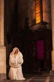 Monje arrodillado en la iglesia oscura — Foto de Stock