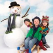 Sledge and snowman fun — Stockfoto