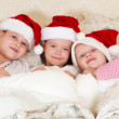 In bed with christmas hats — Stock Photo #33117453