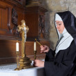 Nun lighting altar candles — Stock Photo