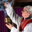 Priest with incense burner — Stock Photo