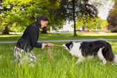 Rope pulling with her dog — Stock Photo