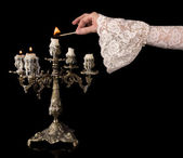 Vintage hand lighting candles — Stockfoto