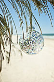 Christmas ball hangs from a tree at the beach — Stock Photo