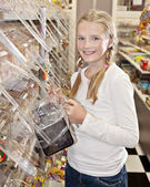 Young girl in candy store, choosing sweets — Stock Photo