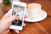 À l'aide de téléphone sur Pause café — Photo