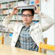 Handsome man in a library — Stock Photo