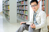 Handsome man sitting and reading in library — Stock Photo