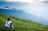 Mountain girl sitting in the lawn of view — Stok fotoğraf