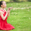 Stock Photo: Red girl blowing dandelion