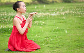 The red girl blowing dandelion — Stock Photo