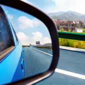 Car rearview mirror and highways — Stok fotoğraf