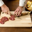 Chef slicing salami, hands detail - Lizenzfreies Foto