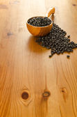 Black beans on wooden background — Stock Photo