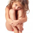 Little girl with matted blond hair sitting and embracing her legs — Stock Photo