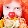 Humble redhead clown with bunch of roses looking at us with kind smile - Zdjęcie stockowe