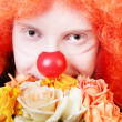 Humble redhead clown with bunch of roses looking at us with kind smile - Stock Photo
