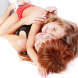 Stock Photo: Mother and her little daughter lying on white background, hugging and having fun