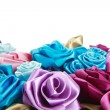 Blue, vinous, pink and turquois handmade silk roses on white background with copy space below — ストック写真