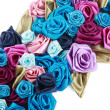 Blue, vinous, pink and turquois handmade silk roses on white background - Stock Photo