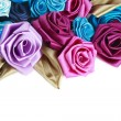 Blue, vinous, pink and turquois handmade silk roses on white background with copy space below - Foto Stock
