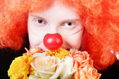 Humble redhead clown with bunch of roses looking at us with kind smile — Stock Photo