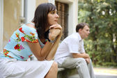 Young woman and man sitting on marble steps in park, selective focus — Stock Photo