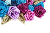 Tet, rosa, blau und türkis handgefertigte seiden rosen auf weißem hintergrund mit textfreiraum unten — Stockfoto