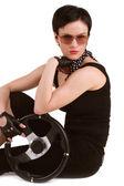 Joven morena en engranaje negro con volante en sus manos — Foto de Stock