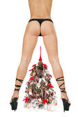 Beautiful woman's bottom and legs in black hyper-sexy stilettos and decorated New Year tree — Stock Photo
