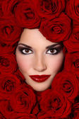 Girl in red roses — Stock Photo