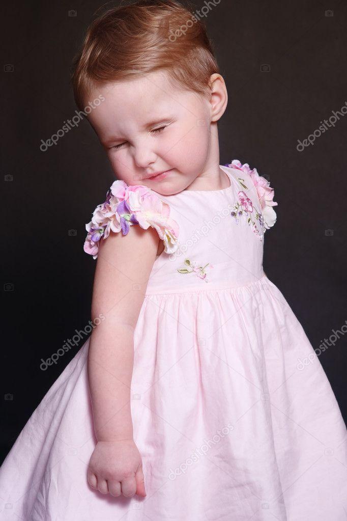 可爱的鬼脸小女孩穿着粉红色衣服的肖像