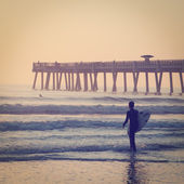 Surfer at the pier. — Photo