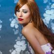 Beautiful redhead on blue vintage background — Stock Photo