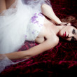 Beautiful and sensual redheaded woman lying on a bed of roses — Stock Photo