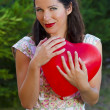 Attractive happy smiling brunette woman hugging one red valentin — Stock Photo