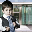 Child dressed businessman smiling in front of building — Stock Photo #12599595