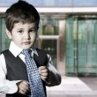 Child dressed businessman smiling in front of building — Stock Photo
